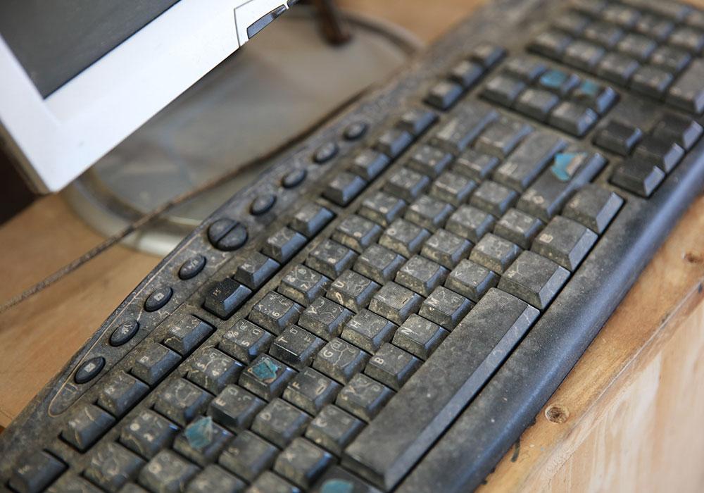dusty dirty keyboard on a wooden desk