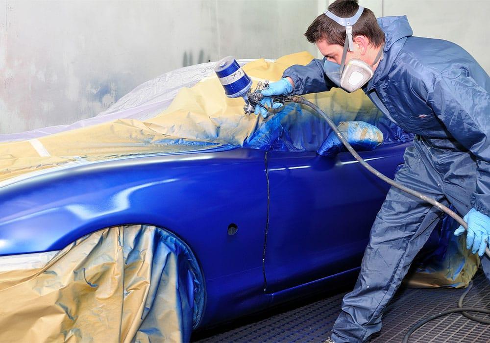 man spraying car paint wearing protective gear