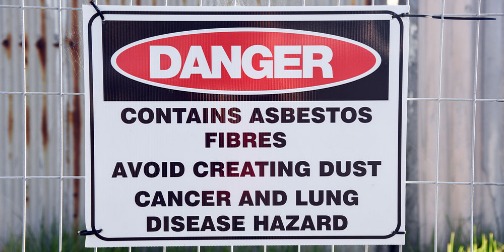 A sign at a construction site warning of the danger of asbestos