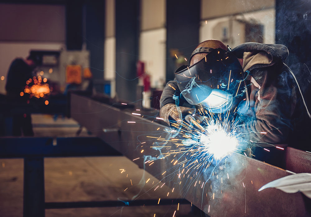 man welding creating fumes and sparks