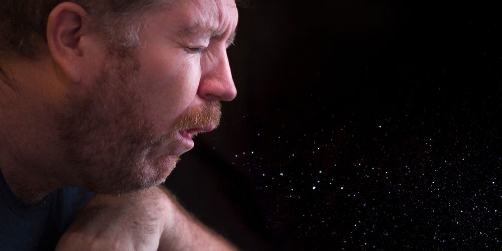 man sneezing and the resulting aerosol spray of bodily fluids